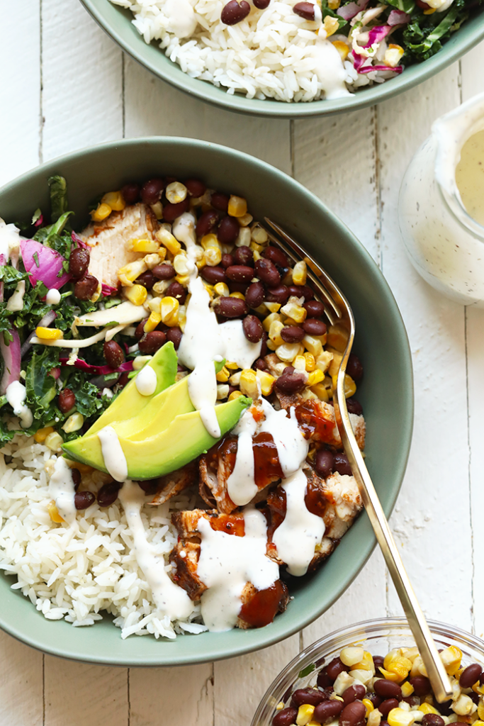 rice topped with bbq chicken, greens, black beans, corn, avocado, and sauce