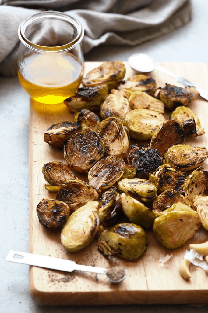 grilled brussel sprouts with balsamic vinegar glaze on a wooden cutting board