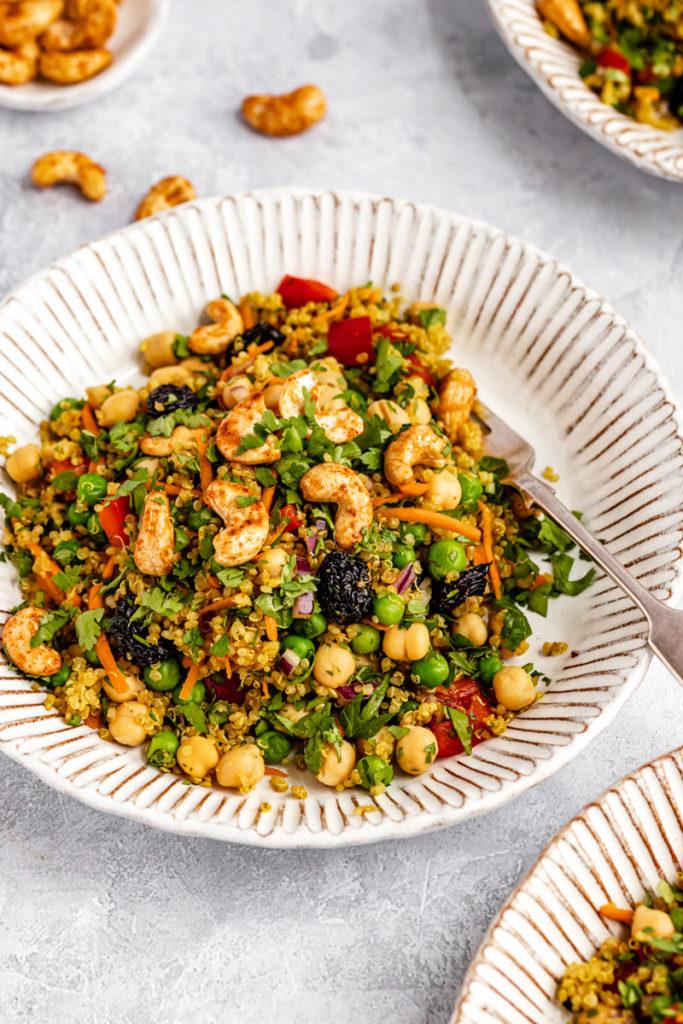chickpeas, cashews, peas, and quinoa in a cream salad bowl