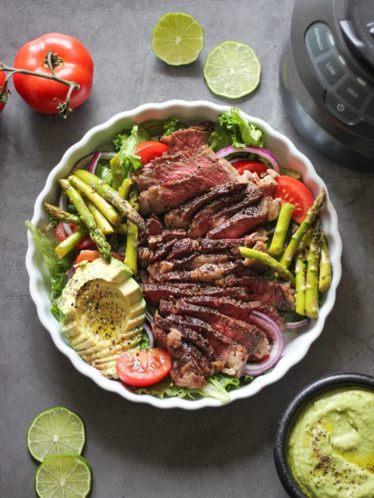 grilled steak on a bed of greens with avocado, grilled asparagus, tomatoes and onions on top