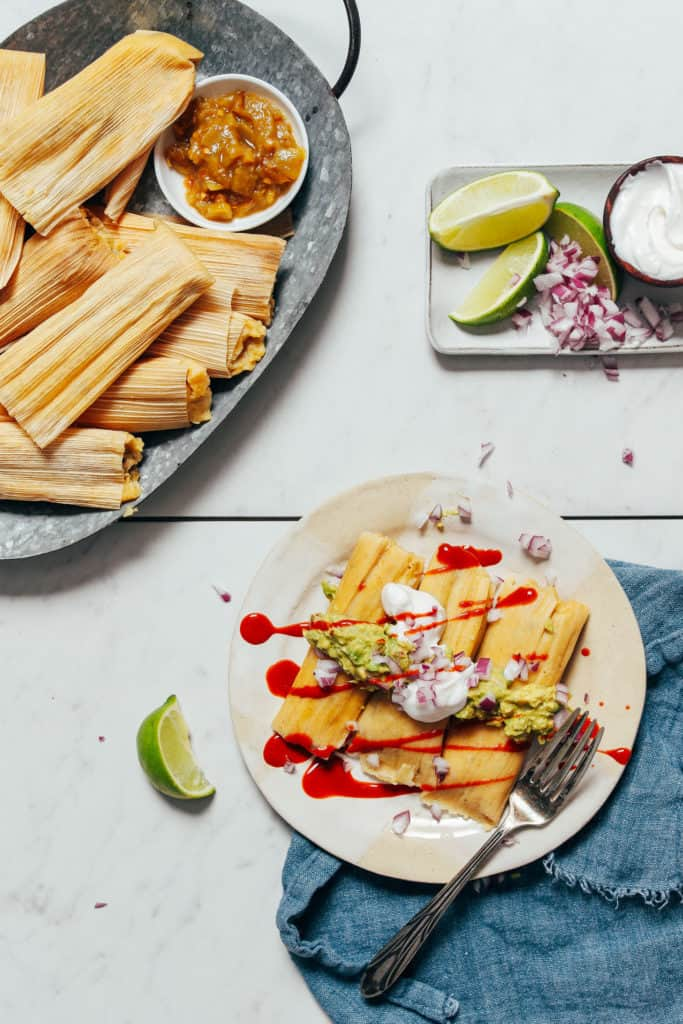 tamales on a white plate topped with guacamole sour green onions and hot sauce next to a plate of tamales