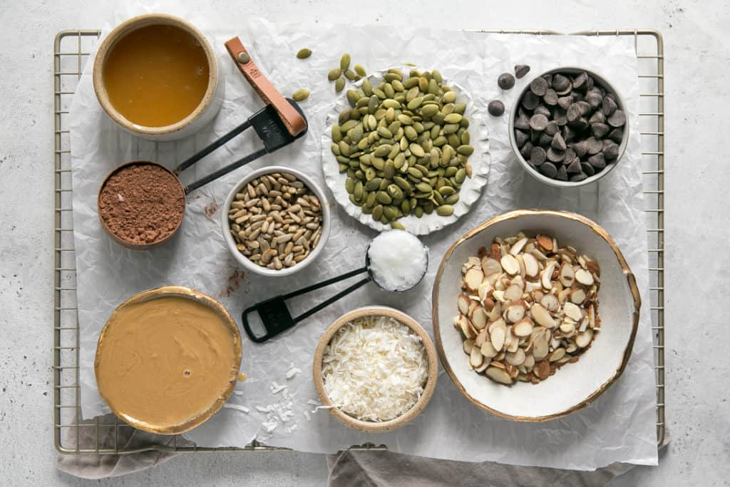 ingredients laid out on wire racks tis parchment paper - oats, nut butter, seeds, chocolate chips, coconut