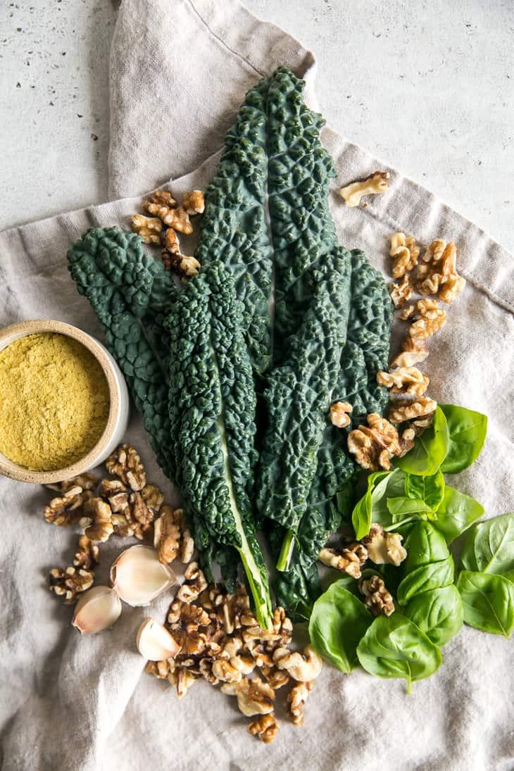 Ingredients on a linen towel - kale, basil, walnuts, garlic, nutritional years
