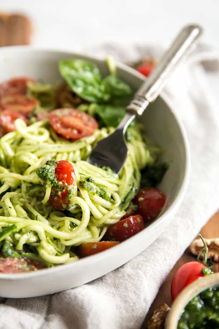 zucchini noodles topped with pesto, tomatoes, and basil in a white bowl and twisted onto a fork