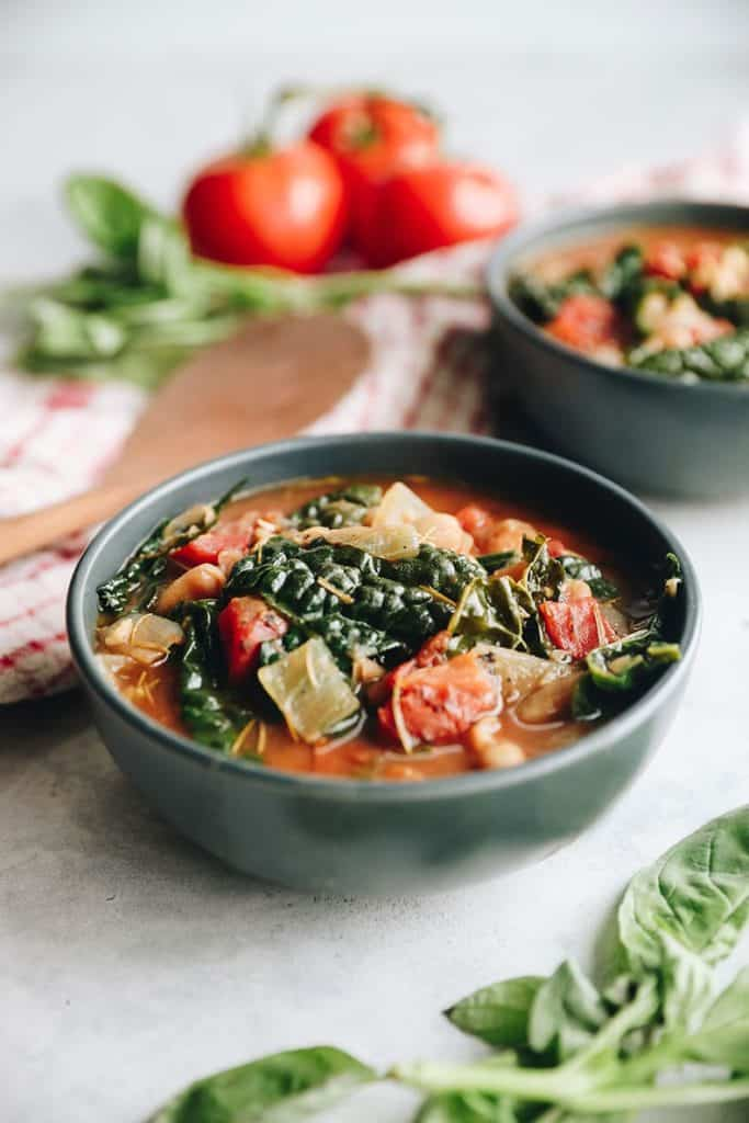 white bean soup with kale in a green bowl