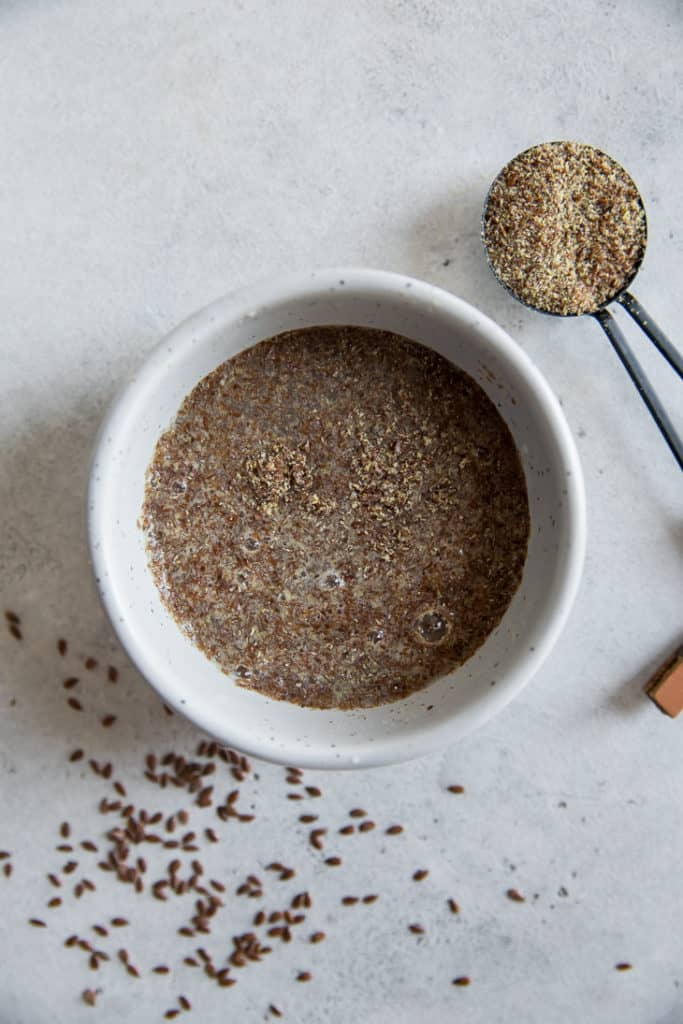 ground flax with water in a white bowl next to a measuring spoon