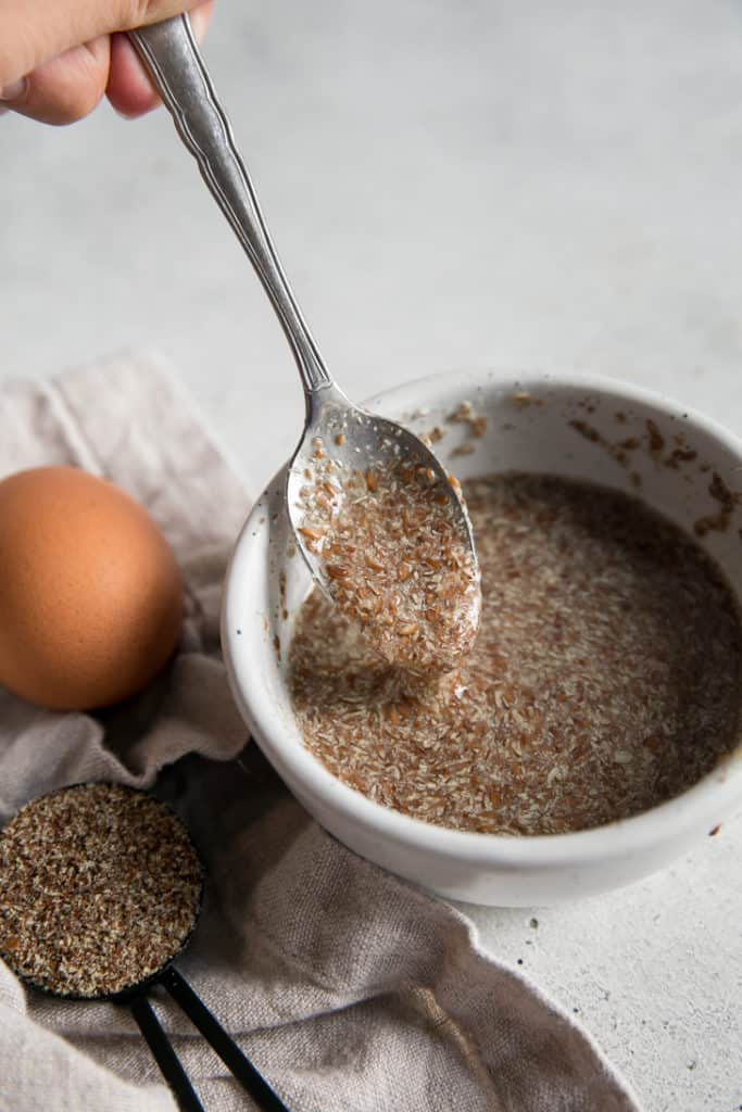 spoon stirring ground flax and water in a small bowl next to a measuring spoon and egg
