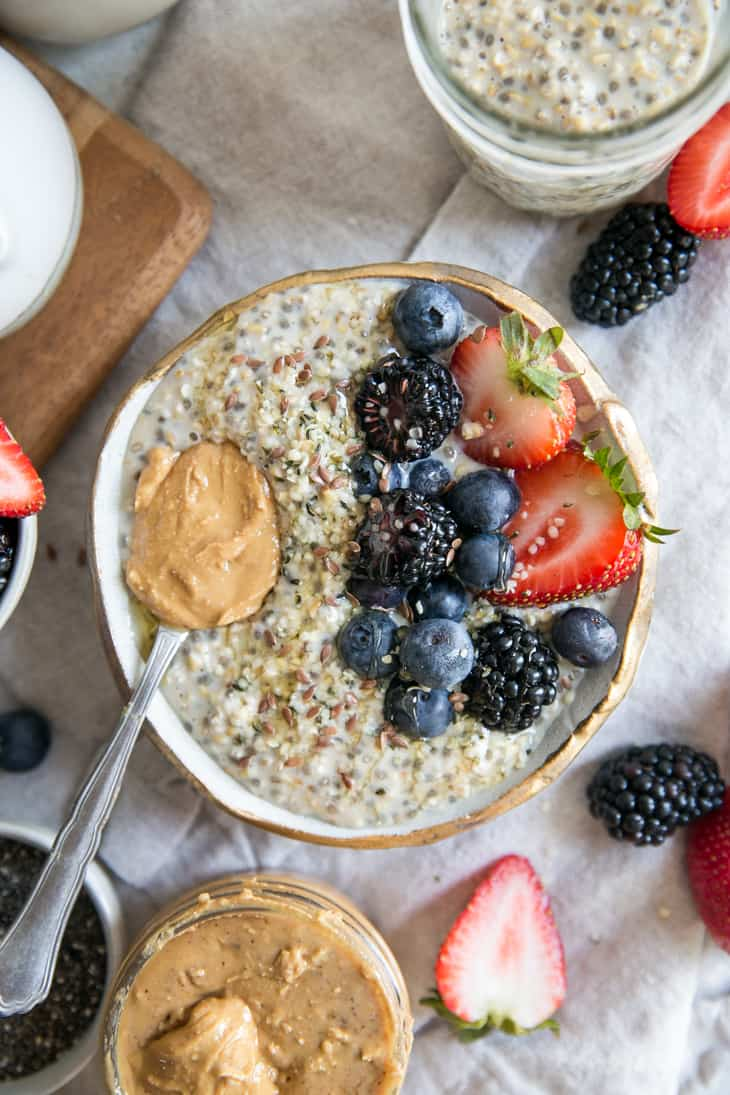 bowl of steel cut oats with fruit and peanut butter on spoon