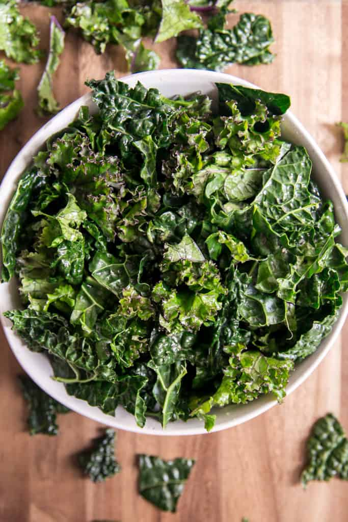 kale in a white bowl on a wood cutting board