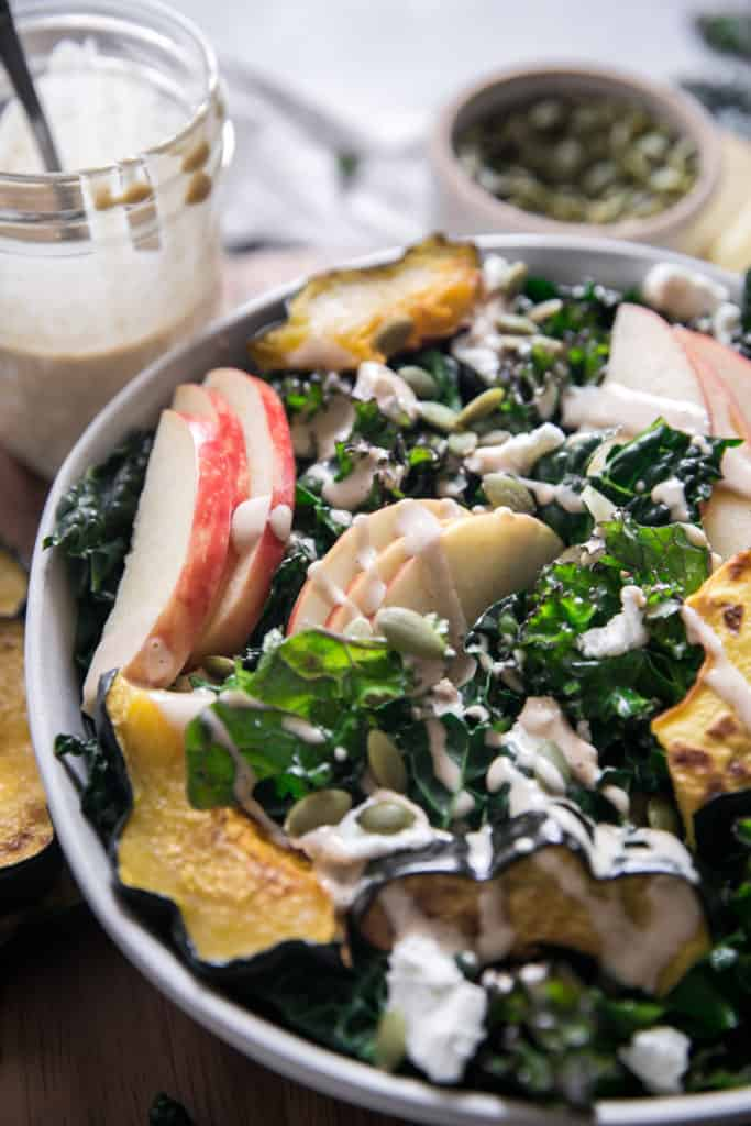 kale apple squash and dressing in a white bowl