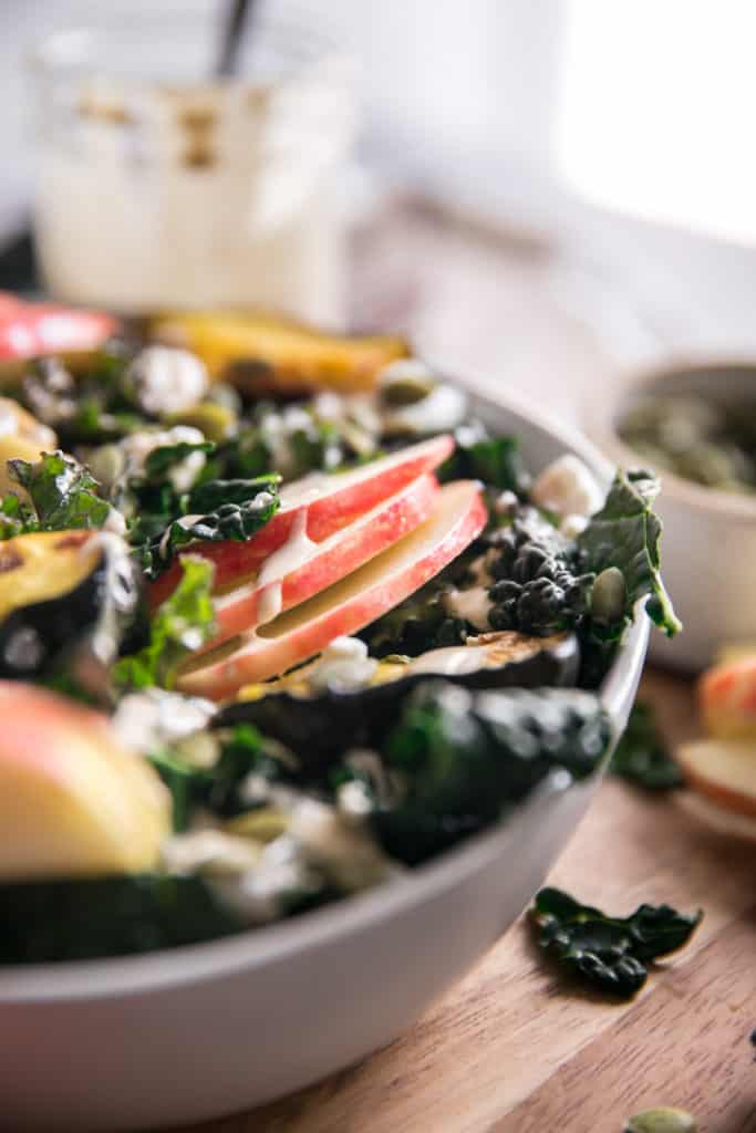 close up of kale apple squash salad in a white bowl