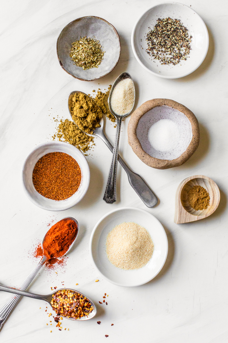 spices in small bowls and spoons on a marble countertop