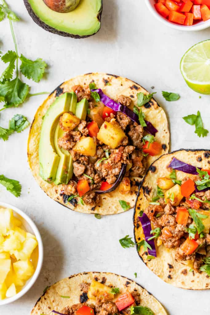turkey tacos topped with pineapple and avocado with cilantro