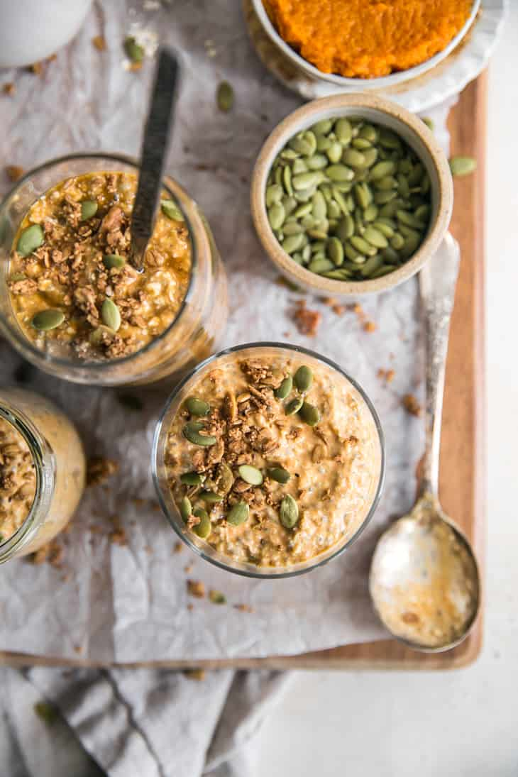 pumpkin oatmeal topped with pepita seeds surrounded by a spoon and bowl of pumpkin puree