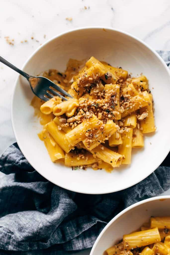 pasta topped with walnuts and herbs in a white bowl