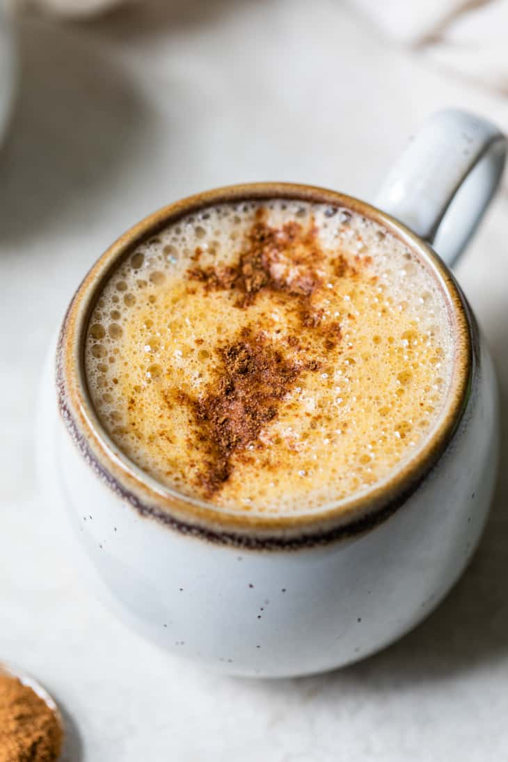 latte topped with cinnamon in a small cream mug