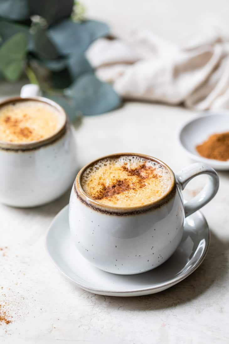 small grey mug on a saucer with a pumpkin spice latte recipe topped with cinnamon