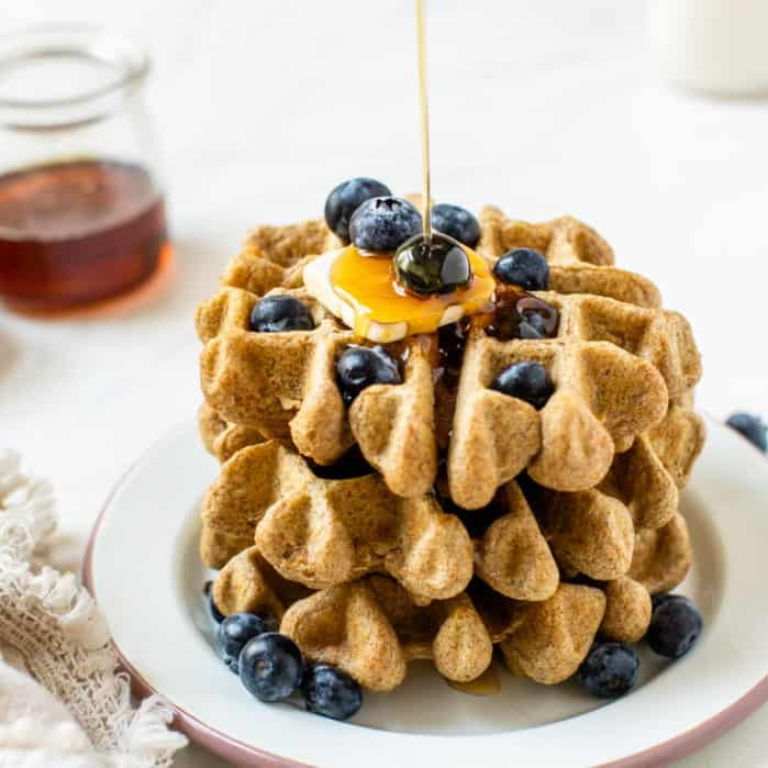 stacked waffles with blueberries and butter