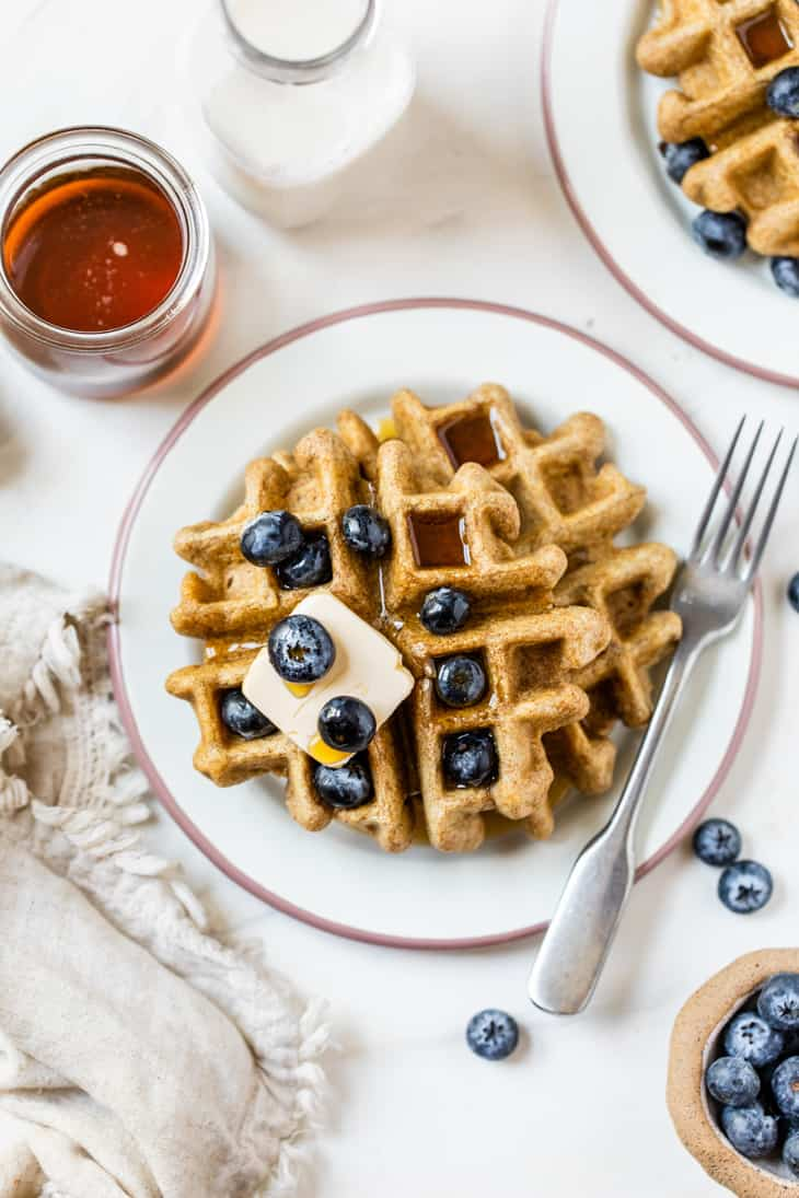 plate of waffles topped with butter syrup and blueberries