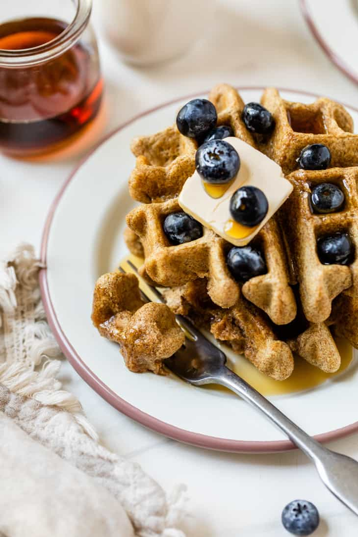 waffles on plate with butter and blueberries