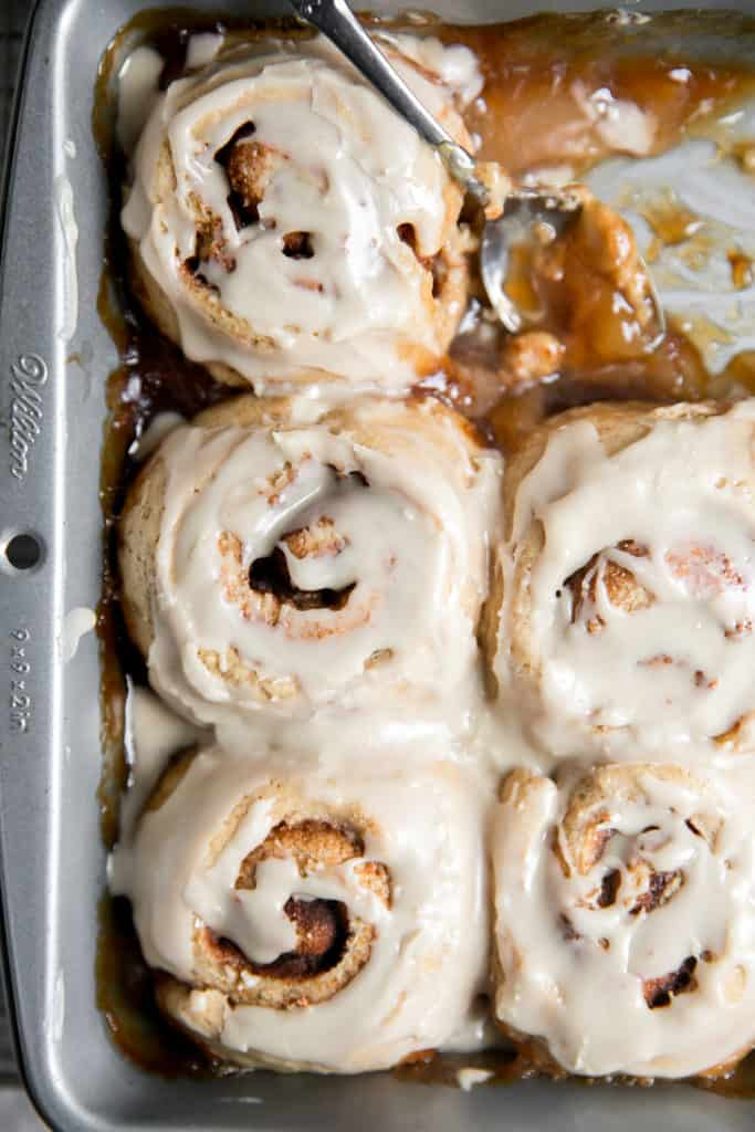 cinnamon rolls in a pan with icing drizzled on top