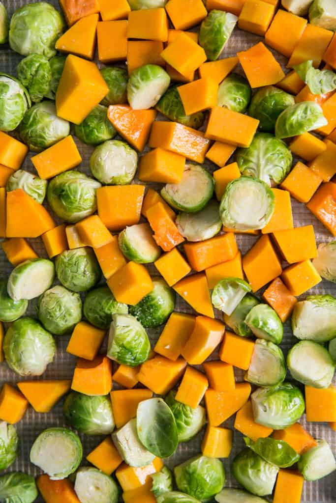 raw cut brussels sprouts and squash on baking pan