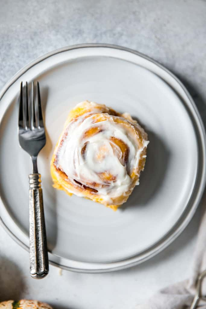 cinnamon roll topped with frosting on a white plate
