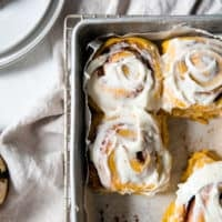 pumpkin cinnamon rolls in pan with frosting