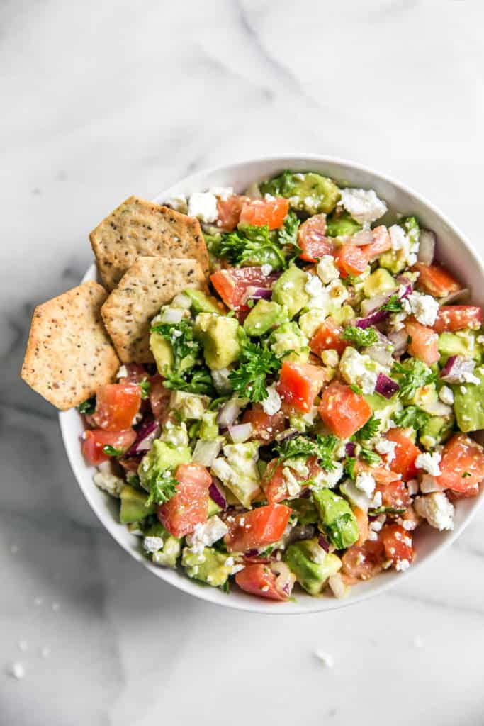 avocado feta tomato onion and cilantro in a white bowl with crackers