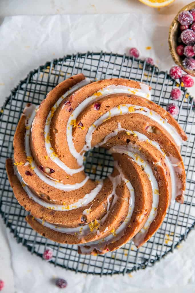 glazed bundt cake on a round wire rack with cranberry around it