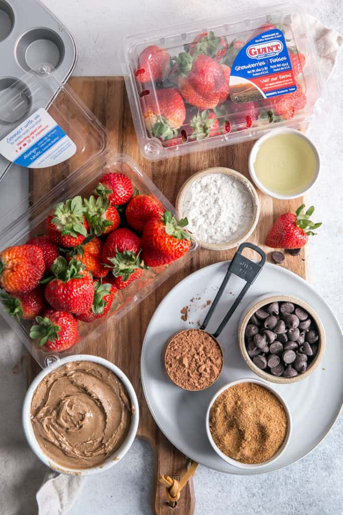 strawberries and brownie ingredients in small measuring bowls on a wooden cutting board
