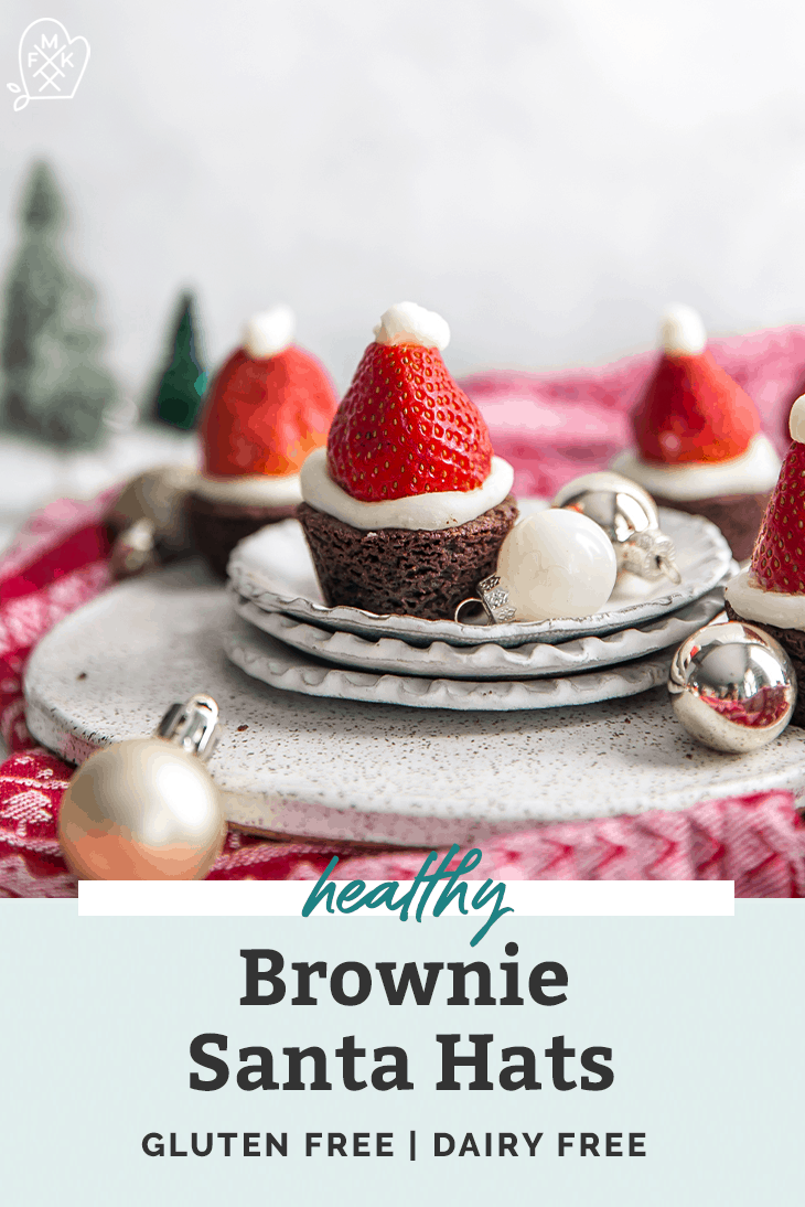 small brownies topped with a santa hate surrounded by a christmas scene