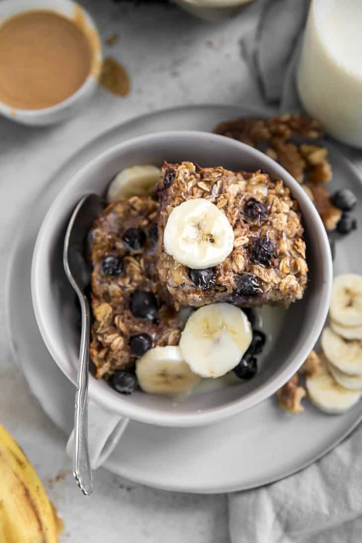 baked banana oatmeal in bowl with banana slices and blueberries