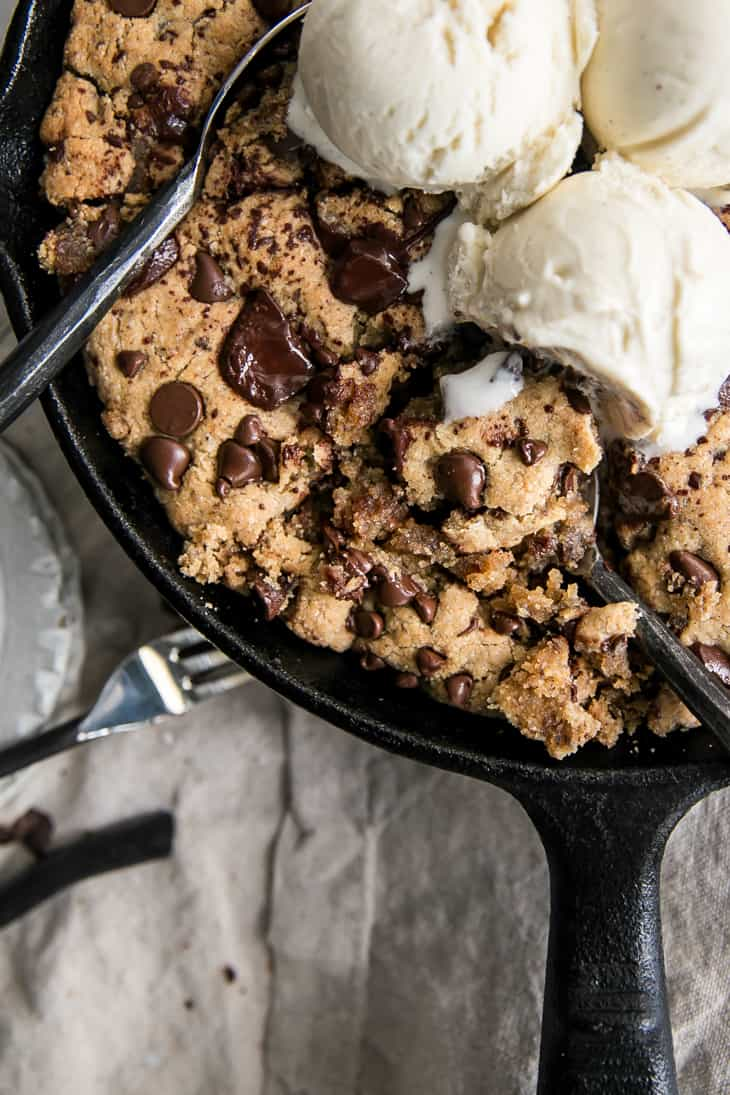 forks into cookie in cast iron skillet with ice cream