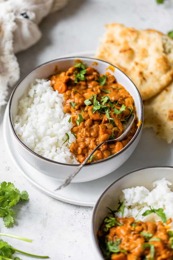 bowl of lentil curry with rice and naan