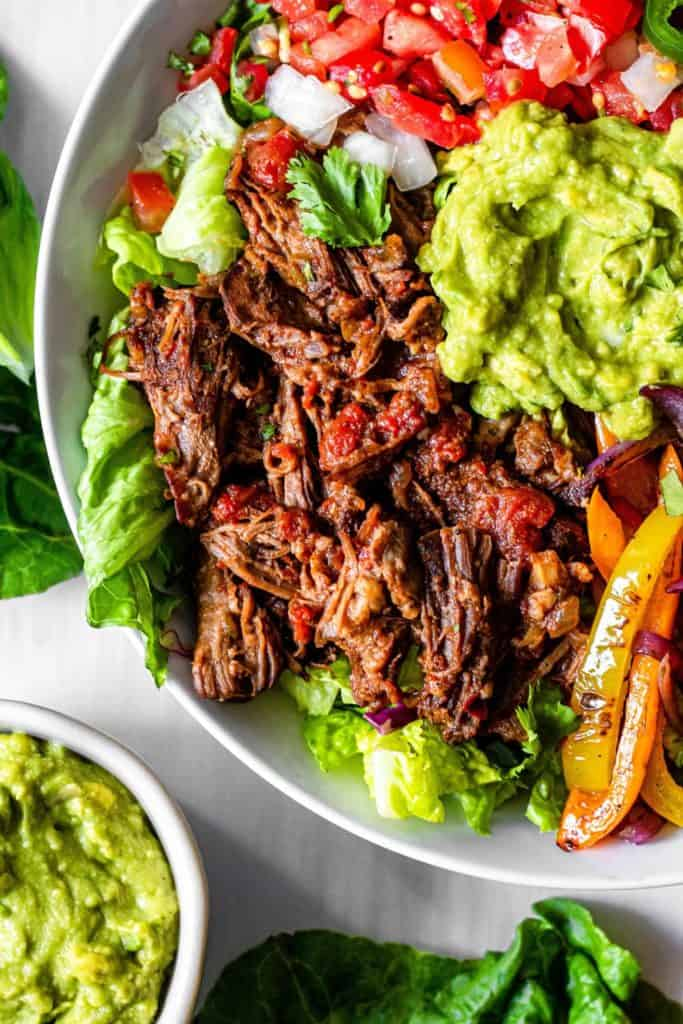 white bowl with lettuce beef guacamole and tomatoes