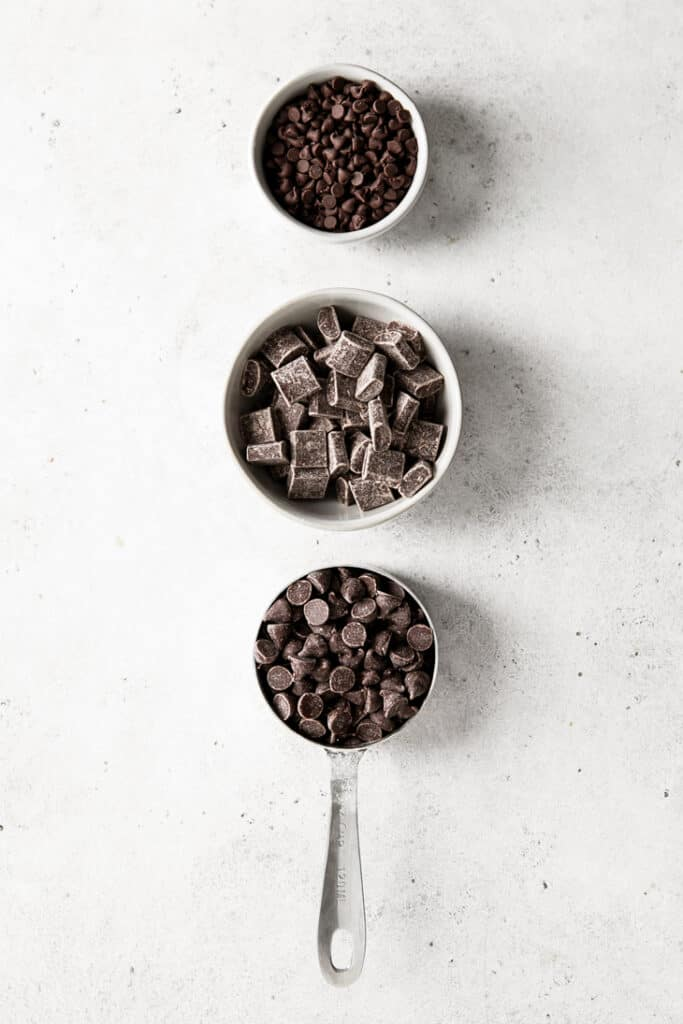 mini chocolate chips, chocolate chunks and chocolate chips in measuring bowls