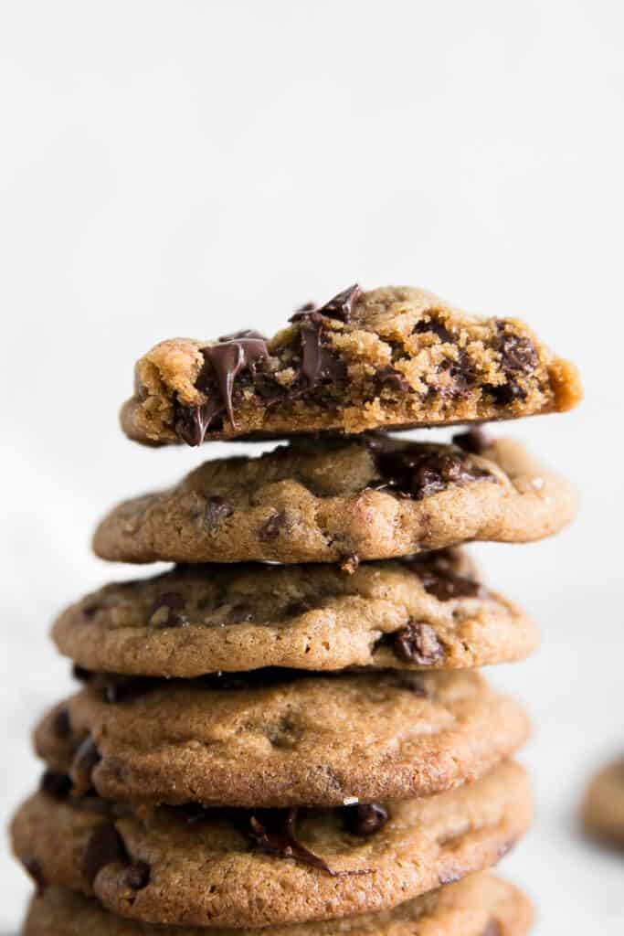 stacked chocolate chip cookies with white background