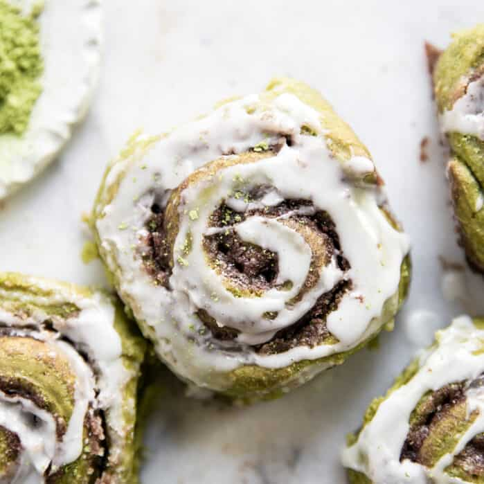 matcha cinnamon rolls on marble with white glaze frosting