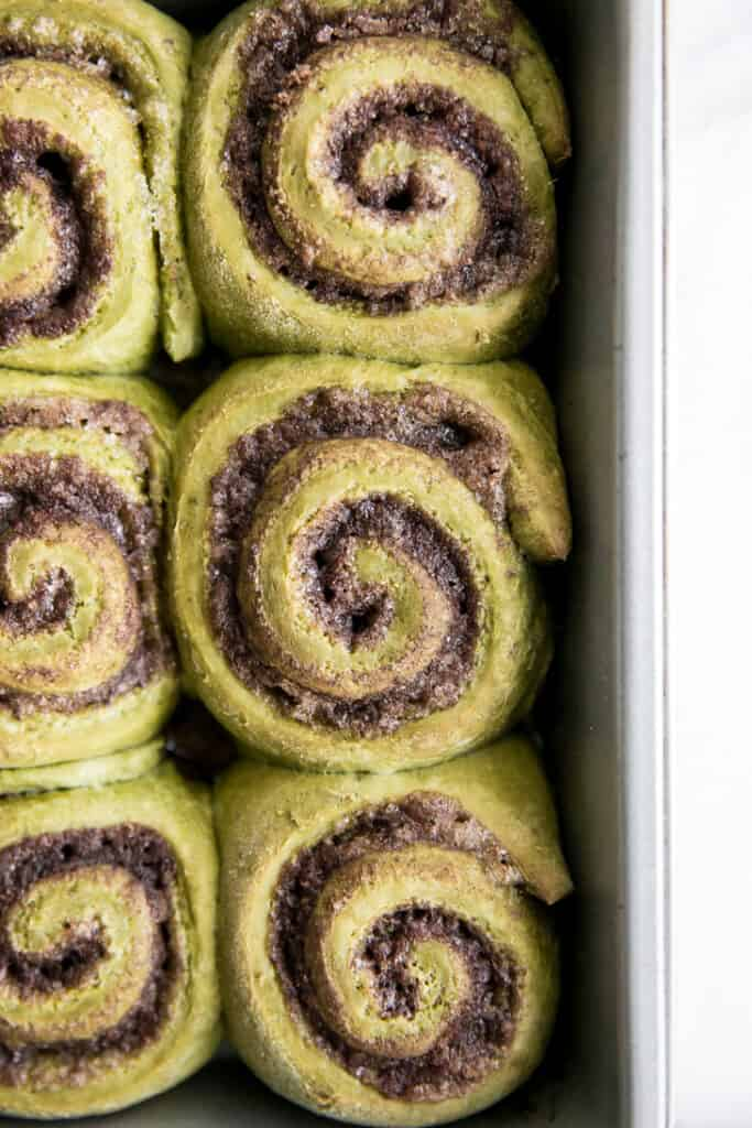 close up of green cinnamon rolls in pan