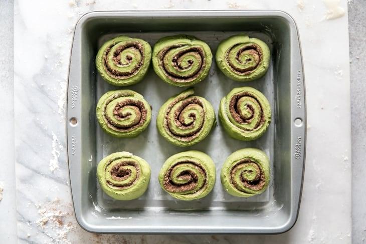 green cinnamon rolls in baking pan
