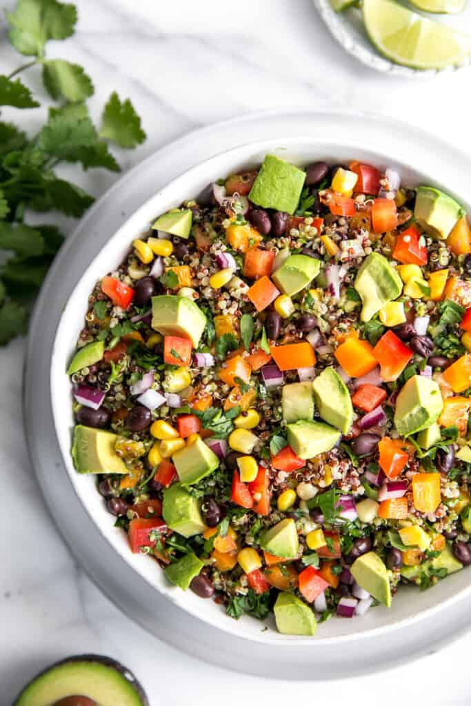 quinoa salad in a white surrounded by cilantro avocado and lime