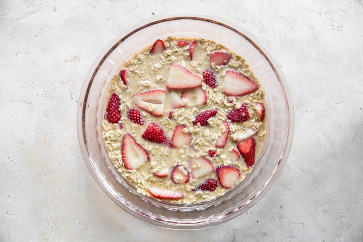 pink pie plate with strawberries topped in oat mixture for baked oatmeal