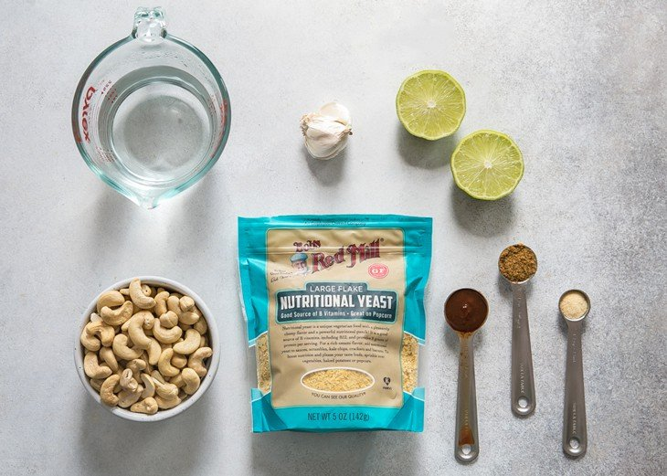 water, cashews, Bob's Red Mill Nutritional Yeast, spices, lime and garlic on gray board