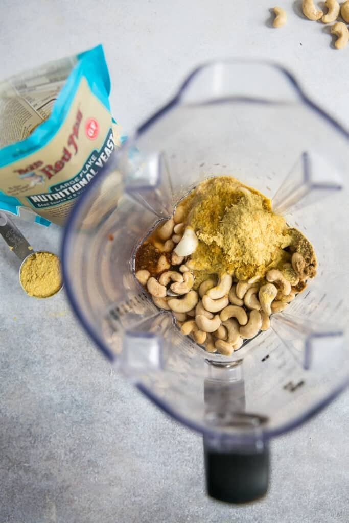 cashews, nutritional yeast and spices in blender for cashew queso