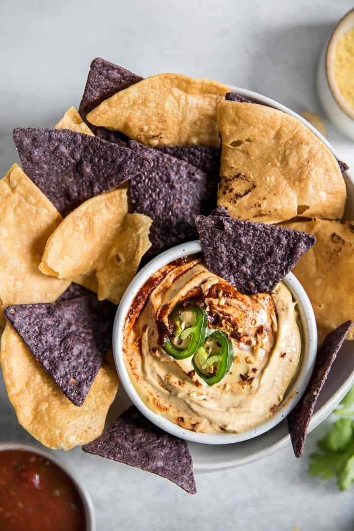 bowl of cashew queso dip with blue and yellow corn chips