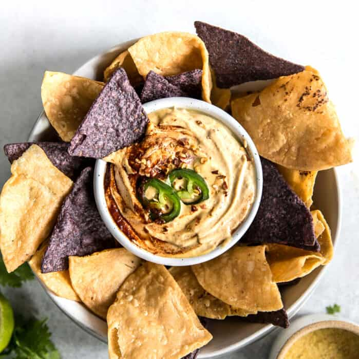 bowl of cashew queso surrounded by blue and yellow corn tortilla chips
