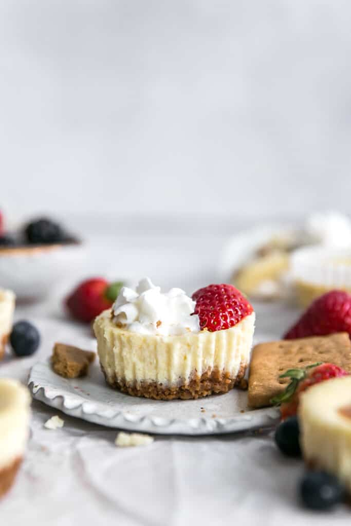 mini cheesecakes on small plate with whipped cream and strawberry