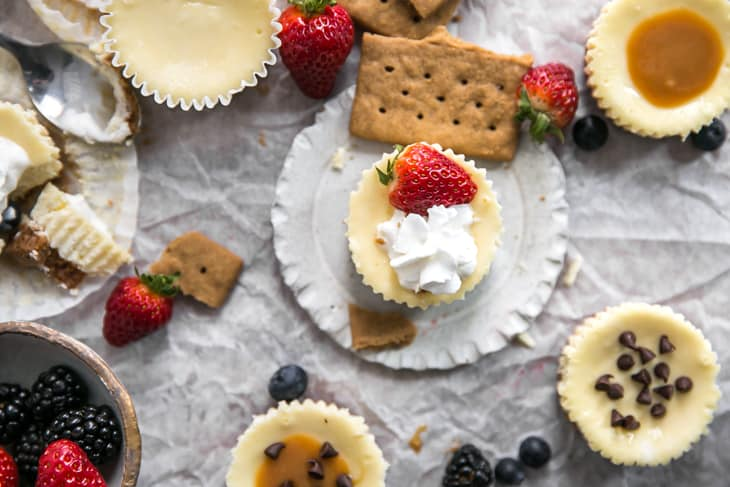 mini cheesecakes with various toppings and strawberries