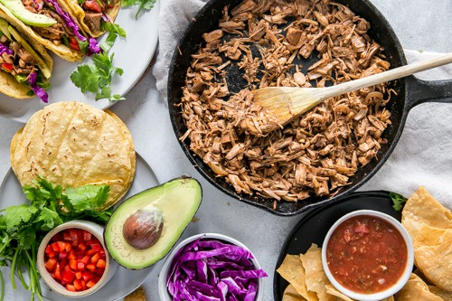 cast iron skillet with jackfruit taco meat and taco toppings on plates
